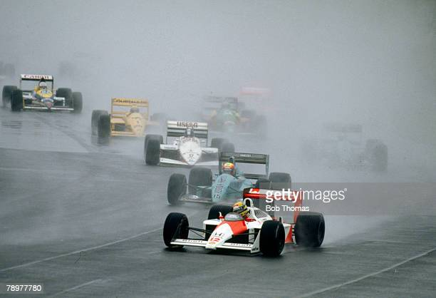 Brazilian racing driver Ayrton Senna drives the Honda Marlboro McLaren McLaren MP4/4 Honda RA168E 15 V6 t in the lead around a rain soaked Copse...