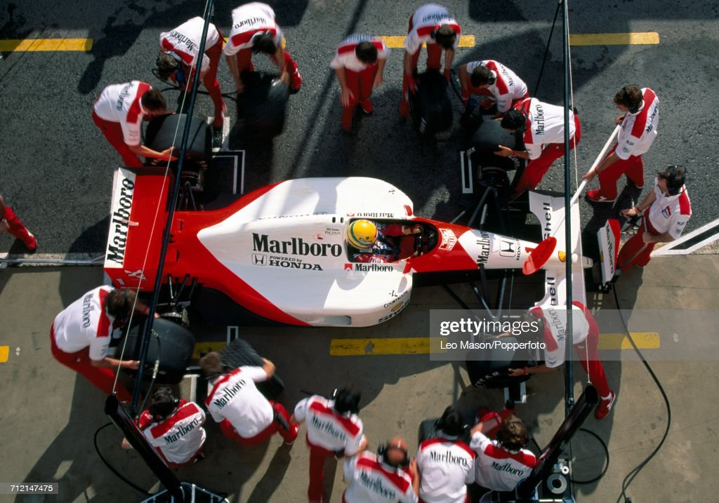 Brazilian racing driver Ayrton Senna (1960-1994) driving a #1 Honda Marlboro McLaren McLaren MP4/6 Honda RA121E 3.5 V12 racing car is surrounded by his pit crew during testing in Jerez, Spain, circa February 1991.