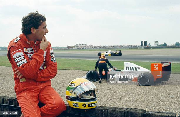 Brazilian racing driver Ayrton Senna watches as his Honda Marlboro McLaren McLaren MP4/5 Honda RA109A 35 V10 is moved by officials after spinning off...