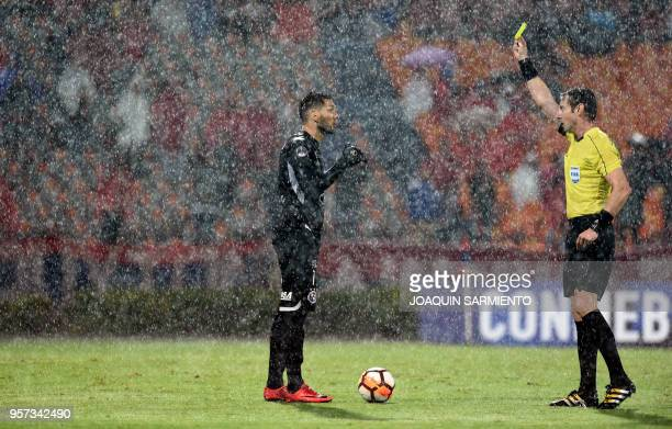 Brazilian referee Raphael Claus shows a yellow card to Paraguay's Sol de America Gerardo Ortiz during a 2018 Copa Sudamericana football match against...