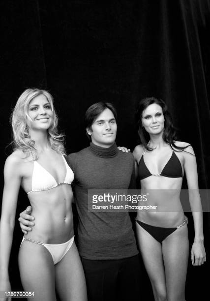 Brazilian Renault Formula One driver Nelson Piquet Junior with two catwalk fashion models before appearing at the Amber Fashion fashion show at the...