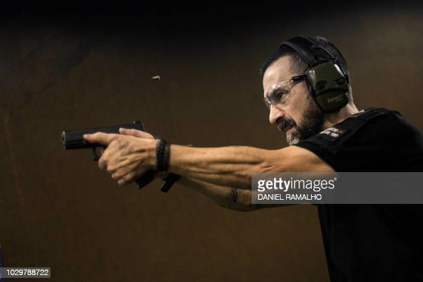 Brazilian reserve militaryman Rildo Anjos shoots at the 'Calibre 12' shooting club where he works as shooting instructor in Sao Goncalo Rio de...