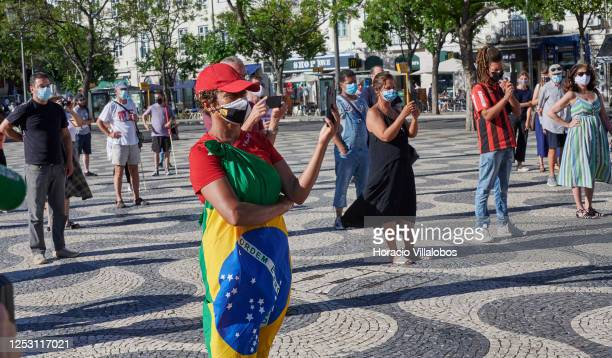 Brazilian residents wear protective masks and keep social distancing while gathering in Praça Rossio to demand the ousting of Brazil's President,...