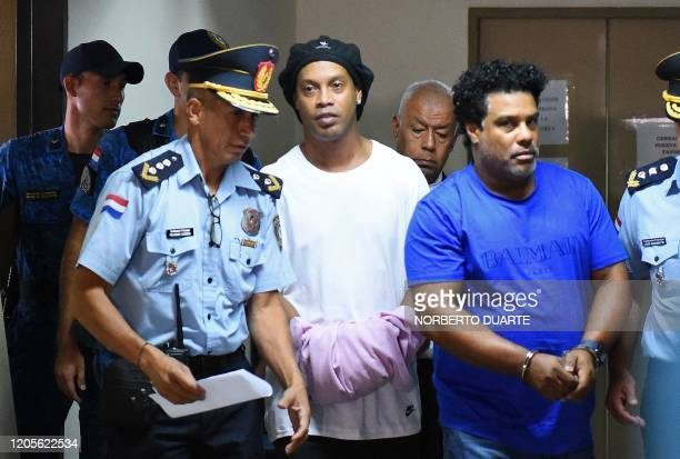TOPSHOT Brazilian retired football player Ronaldinho and his brother Roberto Assis arrive at Asuncion's Justice Palace to appear before a public...