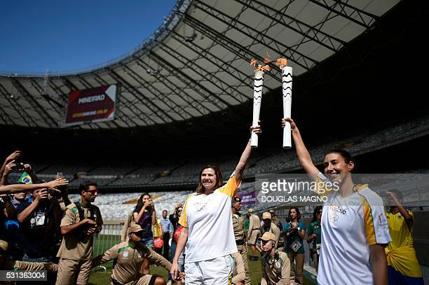 Brazilian retired volleyball player Ana Flavia and Brazilian volleyball player Sheilla Castro hold the olympic torch as it arrives at the Mineirao...