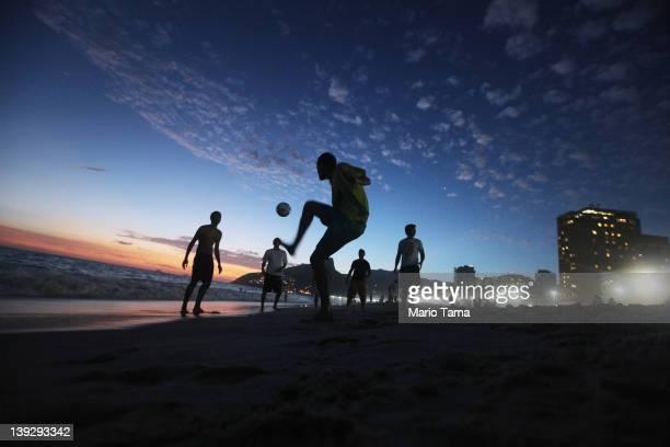 Brazilian revelers play soccer at sunset during Carnival celebrations along Ipanema beach on February 18 2012 in Rio de Janiero Brazil Carnival is...