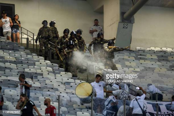 TOPSHOT Brazilian riot police fire rubber bullets and tear gas to supporters of Atletico Mineiro fans after the 2019 Copa Libertadores football match...