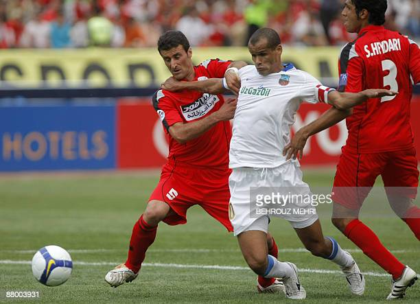 Brazilian Rivaldo of Uzbek champions Bunyodkor is stopped by Iran's Piroozi players Nabiollah Bagheriha and Sepehr Heidari during their AFC Champions...