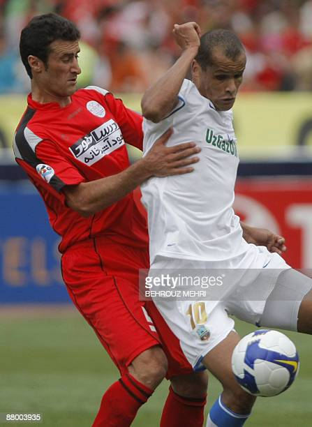 Brazilian Rivaldo of Uzbek champions Bunyodkor is stopped by Iran's Piroozi player Nabiollah Bagheriha during their AFC Champions League round 16...