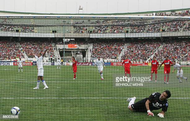 Brazilian Rivaldo of Uzbekistan's Bunyodkor celebrates after scoring a penalty as Iran's Piroozi goalkeeper Misagh Memarzadeh falls on the ground...