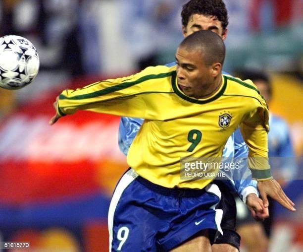 Brazilian Ronaldo fights for the ball against the Uruguayan defense 18 July 1999 El brasileno Ronaldo se lleva la pelota hostigado por un defensor...