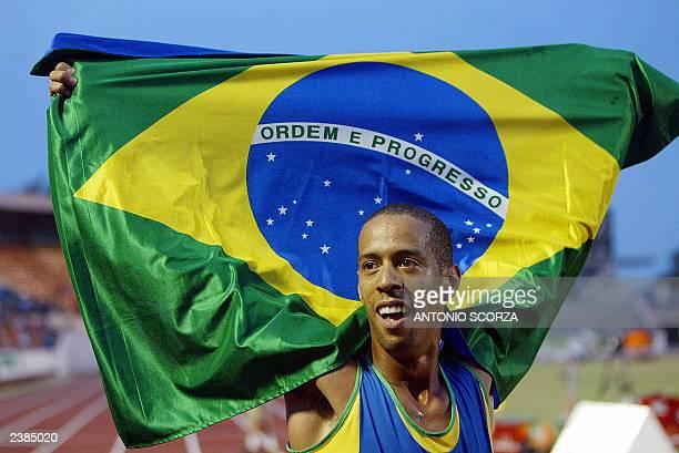 Brazilian runner Hudson de Souza waves his national flag celebrating the gold medal on the men 1500 Mts final 09 August 2003 during the XIV Pan...