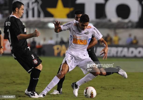 Brazilian Santos player Alan Kardec vies for the ball with Anderson Cardoso of Brazilian's Corinthians during their Copa Libertadores football...