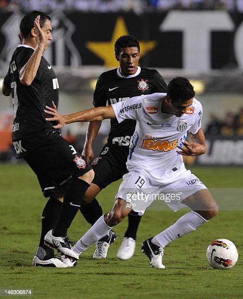 Brazilian Santos player Alan Kardec vies for the ball with Anderson Cardoso and Paulinho Becerra of Brazilian's Corinthians during their Copa...