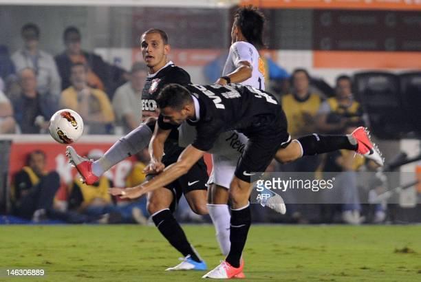 Brazilian Santos player Neymar vies for the ball with Fabio Santos and Leandro Castan of Brazilian's Corinthians during their Copa Libertadores...