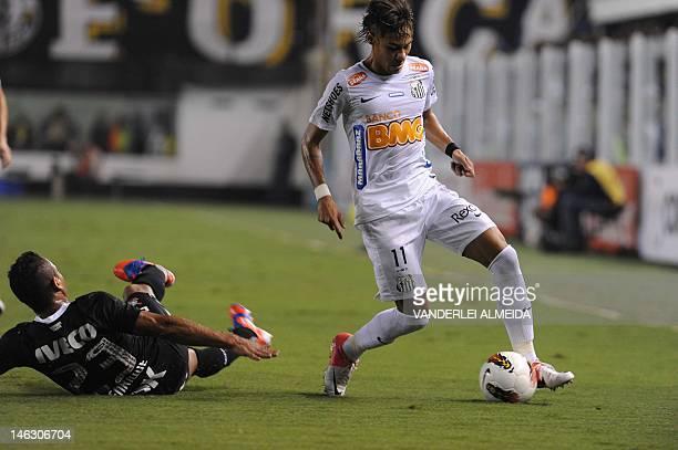 Brazilian Santos' player Neymar vies for the ball with Jorge Henrique of Brazilian Corinthians during their Copa Libertadores first leg semifinal...