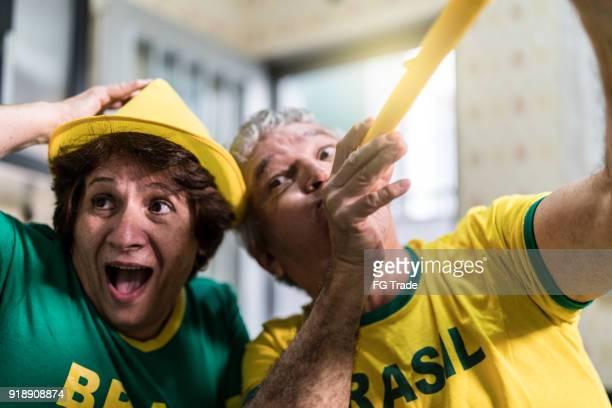 fã brasileiro sênior casal assistindo jogo de futebol em casa - partidário - fotografias e filmes do acervo