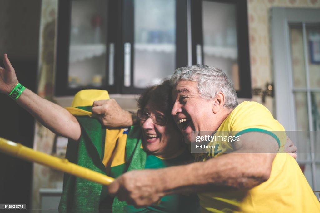 Fã brasileiro sênior casal assistindo jogo de futebol em casa : Foto de stock