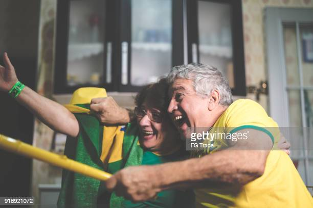 Brazilian senior couple fan watching soccer game at home