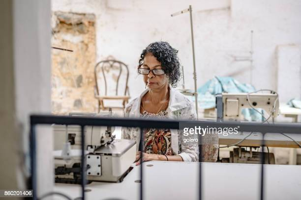 brazilian senior woman at sewing machine in tailor work room