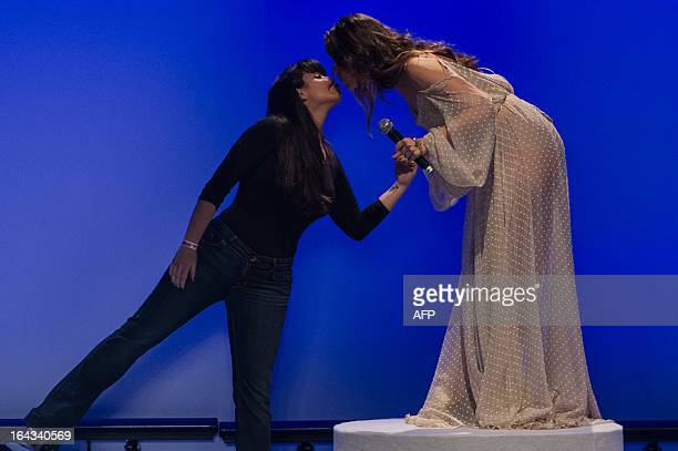 Brazilian singer Roberta Sa and Brazilian designer Helo Rocha greet each other on stage during the 2013 Summer collections of the Sao Paulo Fashion...