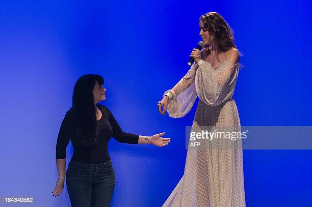 Brazilian singer Roberta Sa sings beside Brazilian designer Helo Rocha on stage during the 2013 Summer collections of the Sao Paulo Fashion Week in...
