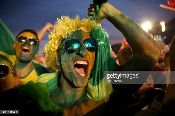 Brazilian soccer fans react to their team scoring their 2nd goal against Cameroon while watching on a screen at the FIFA Fan Fest on Copacabana beach...