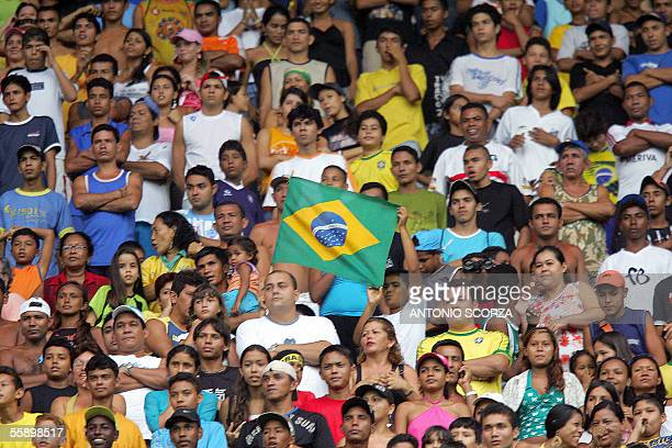 Brazilian soccer fans wave their national flag 11 October 2005 during Brazil's soccer team training session at the Mangueirao stadium in Belem...