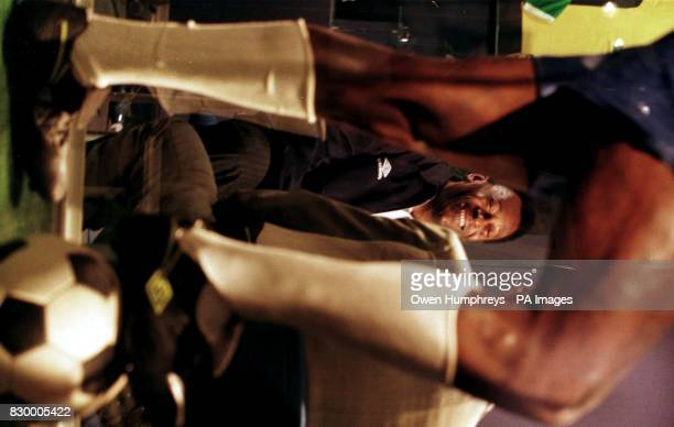 Brazilian soccer legend Pele smiles as he looks up at his wax work double on show today at the new Manchester United Football Club Museum which he is...