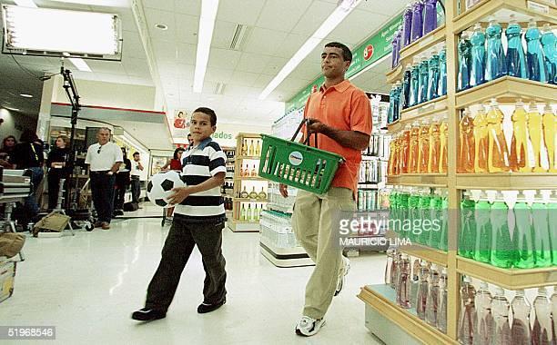 Brazilian soccer player Romario makes a commercial with a child in a supermarket in San Pablo Brazil 09 October 2000 El jugador de la seleccion...