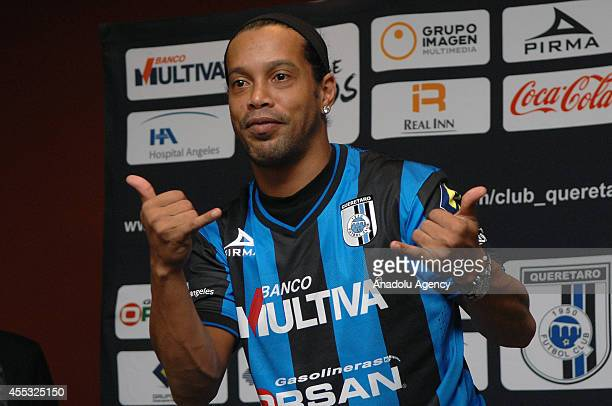 Brazilian soccer player Ronaldinho poses with with his new team Queretaro's jersey during his presentation at Camino Real Hotel in Mexico City, on...