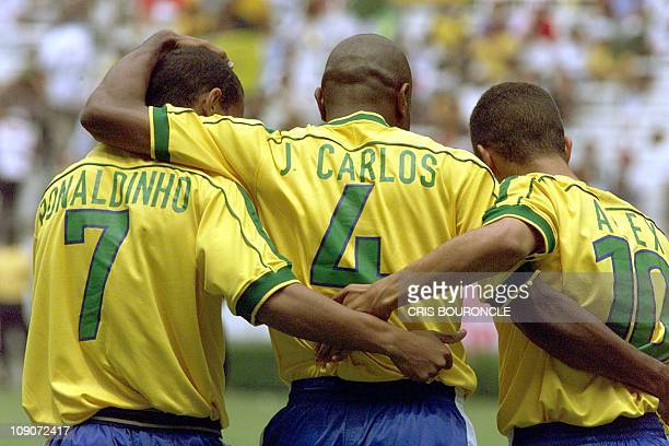 Brazilian soccer players Ronaldinho Ze Roberto and Alex celebrate the goal by Ronaldinho at 0122 minutes of the first half against Saudi Arabia...