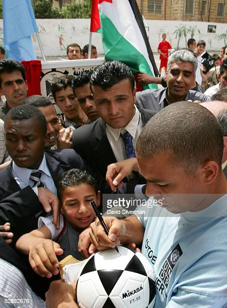 Brazilian soccer star Ronaldo a Real Madrid player signs a Palestinian boy's soccer ball at a center for disadvantaged youth founded by the UN May 16...