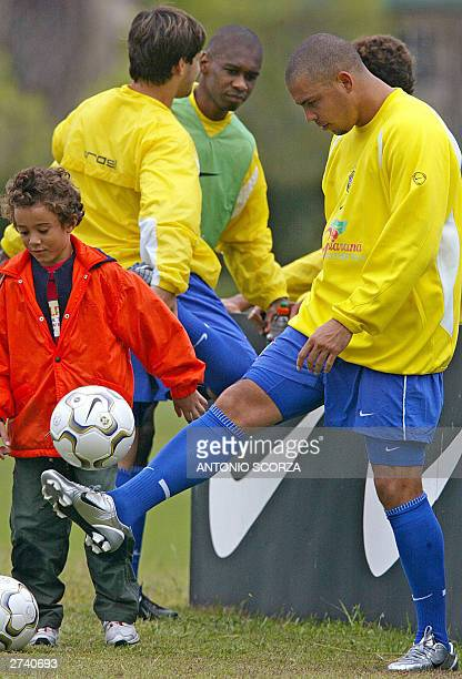 Brazilian soccer striker Ronaldo Nazario controls the ball beside his nephew Caio 14 November 2003 after a trainning session in Teresopolis 130 km to...