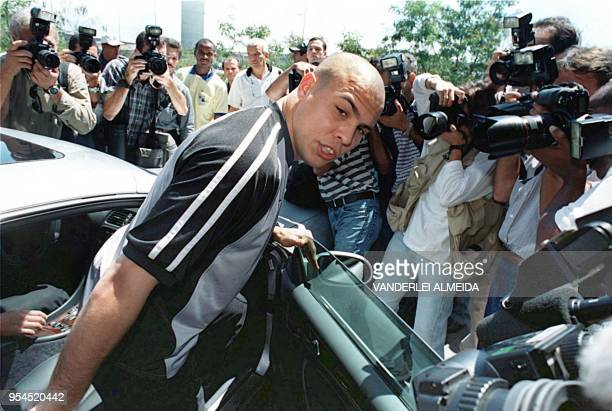 Brazilian soccer superstar Ronaldo is surrounded by photographers as he gets into a car following his arrival at the Tom Jobim Airport in Rio de...