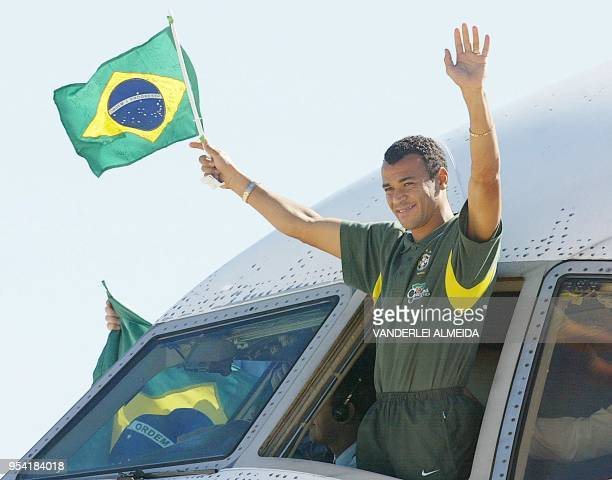 Brazilian soccer team captain Cafu waves a national flag towards the soccer supporters from the cockpit of the aircraft that transported the team to...