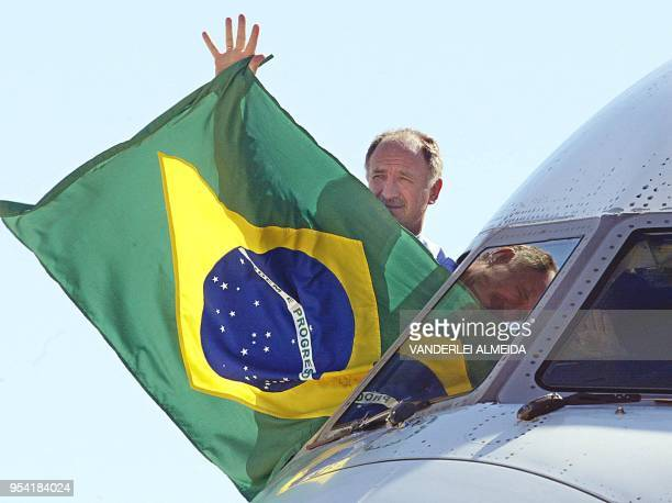 Brazilian soccer team DT Luis Felipe Scolari waves a national flag towards the soccer supporters from the cockpit of the aircraft that transported...