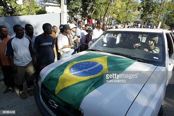 Brazilian soldier drives an SUV with the Brazilian flag past the Haitian Prime Minister's office in PortAuPrince 02 March 2004 Brazilian President...