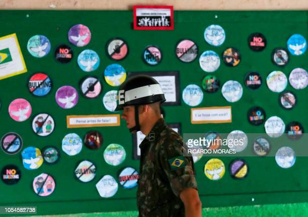 A Brazilian soldier inspects the polling centre where Jair Bolsonaro farright lawmaker and presidential candidate of the Social Liberal Party will...