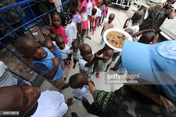 A Brazilian soldier of the MINUSTAH force gives food to Haitian children orphaned by the 2010 earthquake at an orphanage in PortauPrince on March 3...