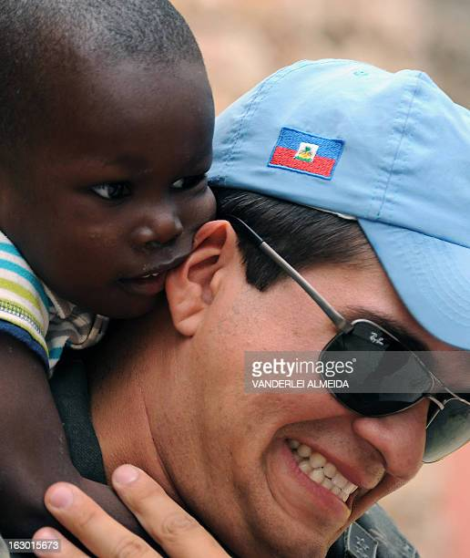 A Brazilian soldier of the MINUSTAH force holds an Haitian child orphaned by the 2010 earthquake in PortauPrince on March 3 2013 Brazil began the...