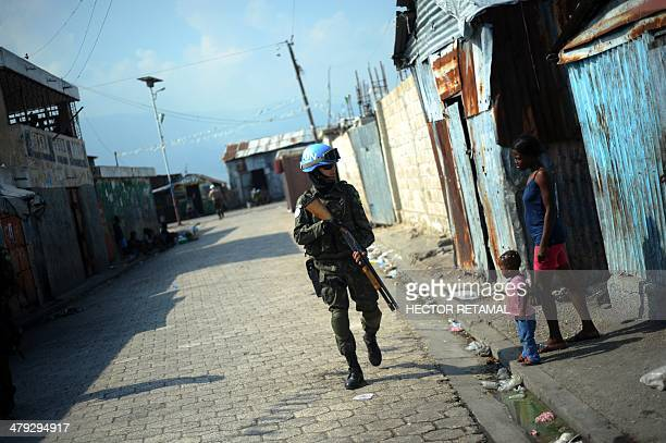 Brazilian soldier of the MINUSTAH peacekeeping contingent patrols in the Cite Soleil slum of Port-au-Prince on March 11, 2014. The Brazilian...