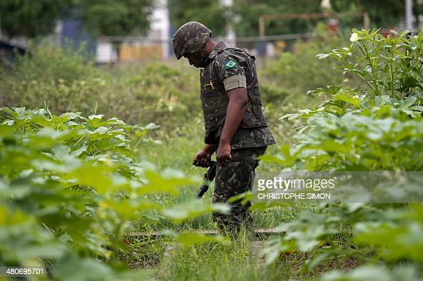 A Brazilian soldier with a metal detector searches for buried weapons in the Favela da Mare slum complex in the northern surburbs of Rio de Janeiro...