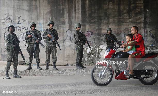 Brazilian soldiers keep watch as people ride motorcycles in the Complexo da Mare 'favela' complex one of the largest 'favela' complexes in Rio on...