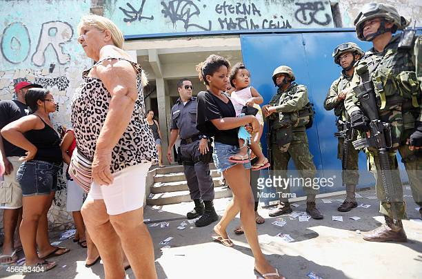 Brazilian soldiers keep watch as people wait to enter a polling station in the Complexo da Mare favela or community on the day of national elections...