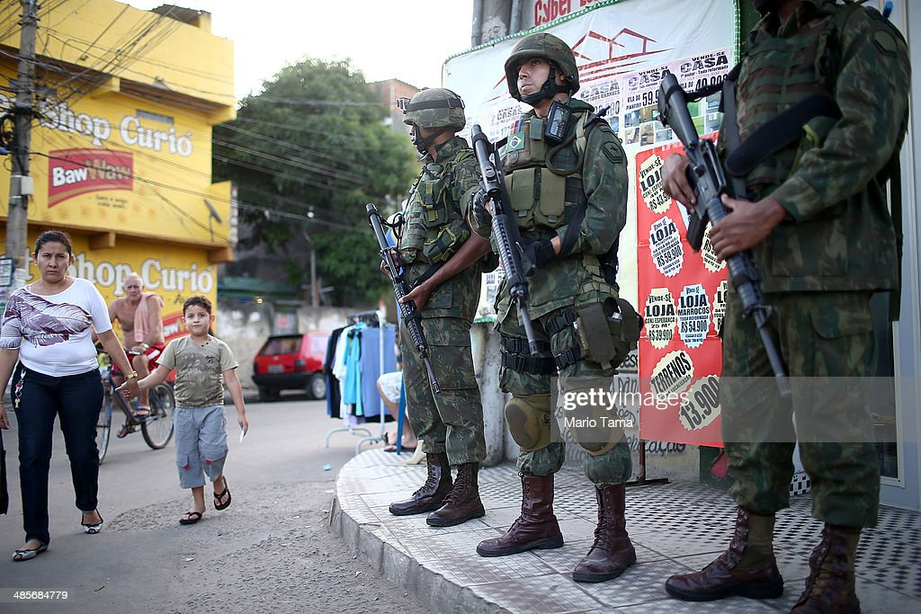 Brazilian soldiers keep watch in the occupied Complexo da Mare, one of the largest 'favela' complexes in Rio, on April 19, 2014 in Rio de Janeiro, Brazil. The Brazilian government has deployed nearly 3,000 federal troops to occupy the group of violence-plagued slums ahead of the June 12 start of the 2014 FIFA World Cup. The group of 16 communities house around 130,000 residents and had been dominated by drug gangs and militias. Mare is located close to Rio's international airport and has been mentioned as a likely pacification target for the police amid the city's efforts to improve security ahead of the 2014 FIFA World Cup and Rio 2016 Olympic Games.