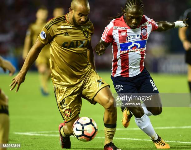 Brazilian Sport Recife midfielder Patrick vies for the ball with Colombian Junior forward Yimmi Chara during their Copa Sudamericana quarterfinals...