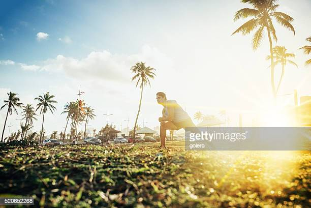 Brasileira desportista alongamentos no Trópico na pôr do sol Costa