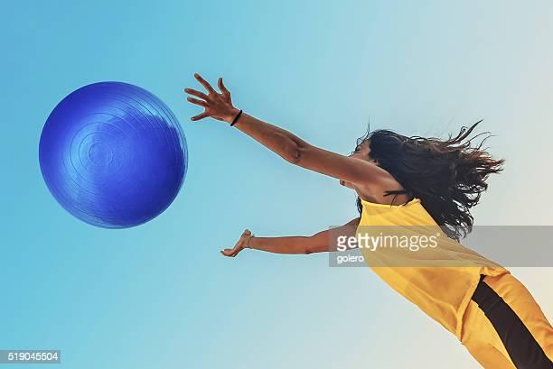 ブラジル スポーツウーマン に黄色のシャツで大きなボールブルージャンプ - つかまえる ストックフォトと画像