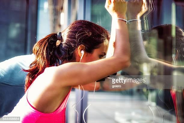 Brasilianische Sportlerin laeaning auf Glas-Fassade nach